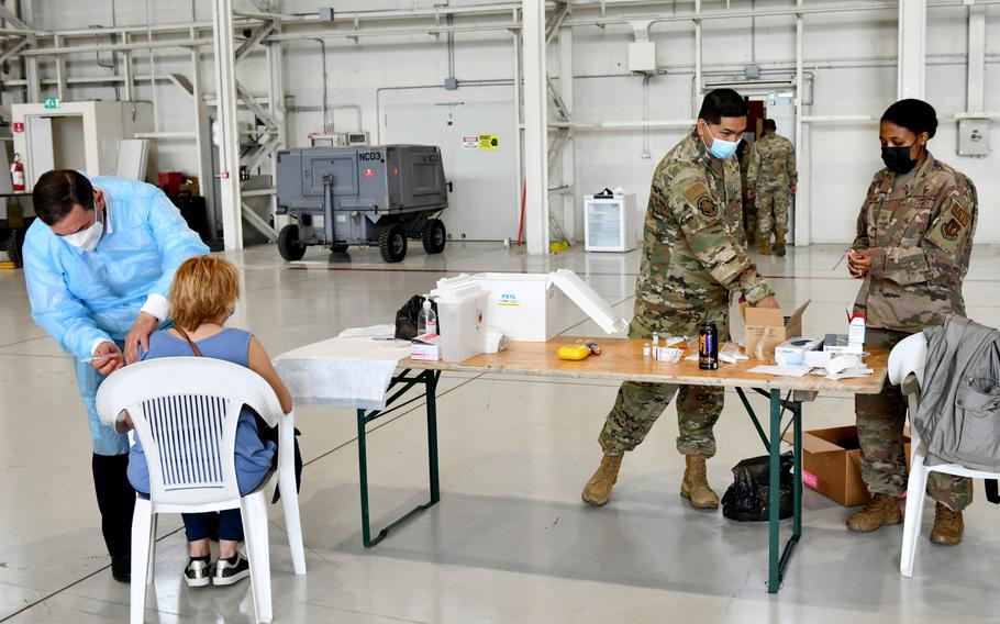 U.S. airmen assigned to the 31st Medical Group prepare syringes with the Moderna COVID-19 vaccine while a local national employee of the base receives her first dose at Aviano Air Base, Italy, April 30, 2021.