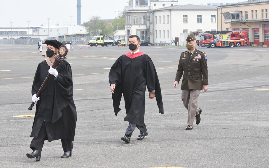 Commencement speakers for the University of Maryland Global Campus Europe class of 2021, including  Tony Cho, middle, UMGC Europe vice president and director, and Gen. Christopher Cavoli, the commander of U.S. Army Europe and Africa, walk across the airfield on Clay Kaserne in Wiesbaden, Germany, towards the stage on May 1, 2021.