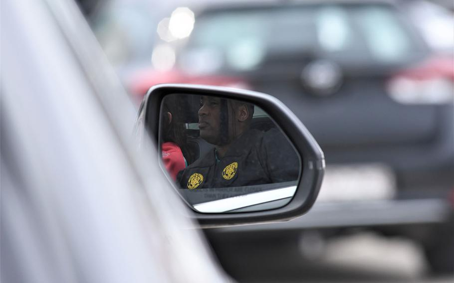A graduate sits in his car on the airfield on Clay Kaserne in Wiesbaden, Germany, waiting to be called up to the stage. The University of Maryland Global Campus Europe held a drive-in movie style commencement ceremony for the class of 2021 on Saturday, May 1, 2021.