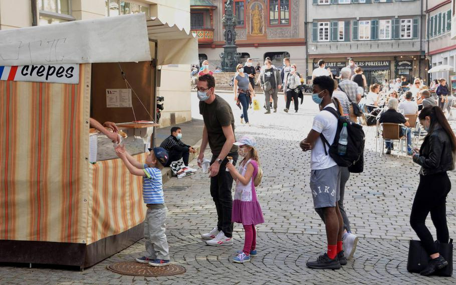 A boy is handed a crepe at a stand just off Marktplatz in Tuebingen, Germany, on March 30, 2021. German Health Minister Jens Spahn said May 7, 2021, that businesses can cautiously reopen, starting by offering outdoor dining and events, but only when new cases fall below 100 per 100,000 residents per week.