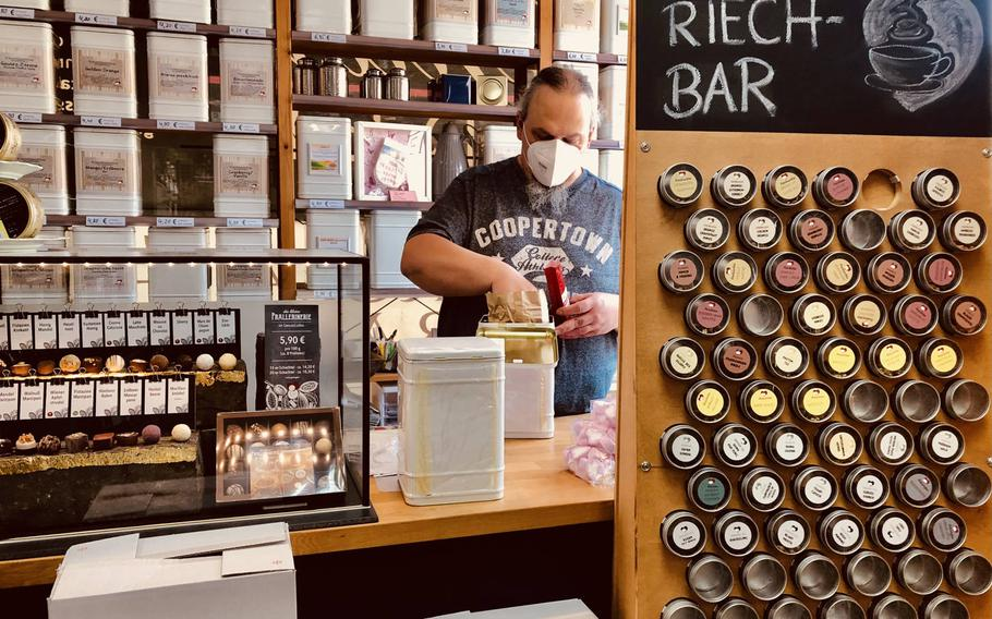 The shopkeeper at the Genussladen in Altenglan, Germany, wears a face mask as he scoops tea into a bag for a customer. German health authorities said May 7, 2021, they think the third wave of the coronavirus has been halted in Germany, but warned that it could resurge if people let down their guard.