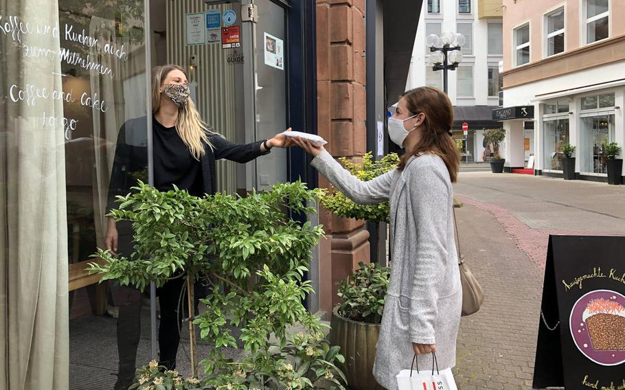 A customer picks up a slice of cake at Cafe Susann in Kaiserslautern, Germany, during the first wave of the coronavirus, May 8, 2020. A year later, Germany was in a third wave of the virus and most eateries were still doing takeout only.
