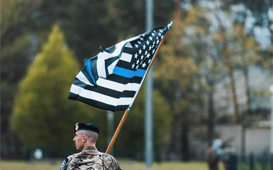 A screenshot of a photo on Ramstein Air Base's Facebook page Tuesday shows a security forces airman carrying a black-and-white American flag with a blue line through it. The photo was posted to show support for the airmen during National Police Week. It was taken down after the base said it violated a Pentagon policy on what types of flags may be displayed on U.S. military installations.