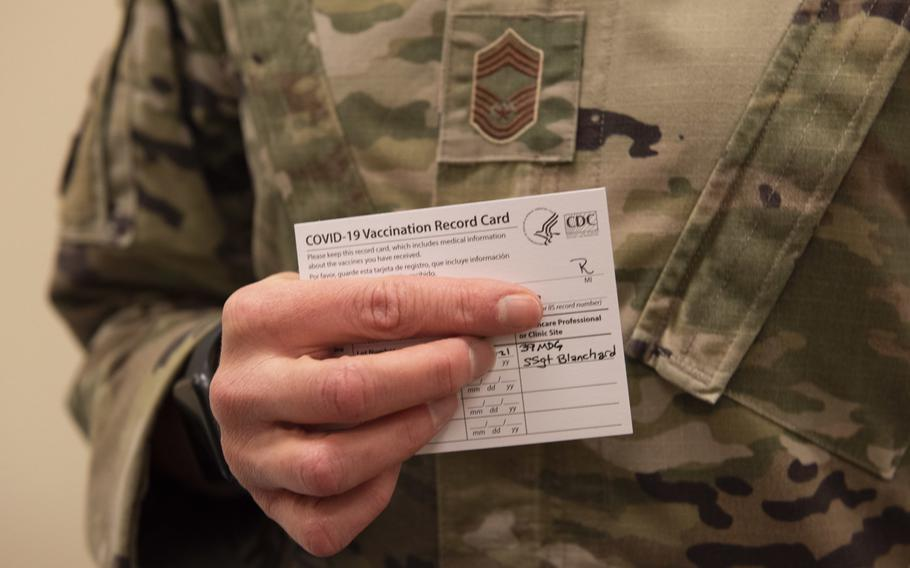 A U.S. airman holds a COVID-19 vaccination card during the first phase of immunizations on Jan. 8, 2021, at Incirlik Air Base, Turkey. Travelers to Germany from Turkey only have to quarantine for five days as of May 13, 2021, and travelers from the U.S. don't need to quarantine at all if they are fully inoculated or can show they have recovered from the virus.