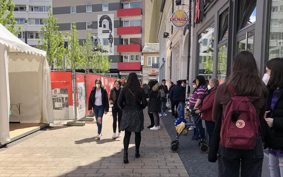 People wait in line for a free coronavirus antigen test in Schillerplatz, downtown Kaiserslautern, Germany, on May 17, 2021. U.S. service members, contractors and their families, who previously paid for the tests, can access them free-of-charge once a week, German health officials said.
