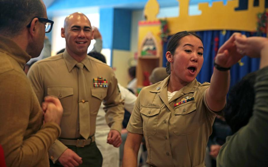 A Marine and a sailor dance with students during a Christmas party at a school in Acireale, Italy, Dec. 11, 2018. An Italian decree states that people are not allowed to dance in public through Sept. 7, 2020 due to coronavirus concerns. U.S. bases in the country are complying with the rule.