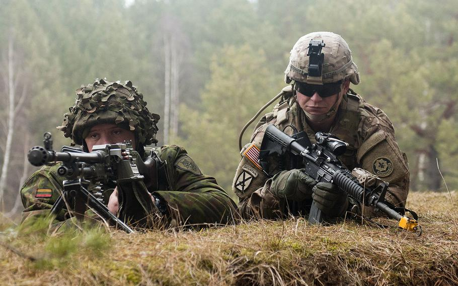 Spc. Shawn Betschart, right, of the 2nd Cavalry Regiment, secures the perimeter with a Lithuanian counterpart during an exercise in Lithuania in 2015. Lithuania's Defense Ministry said this week that the coronavirus pandemic has created conditions for disinformation campaigns aimed at discrediting the NATO alliance to grow.