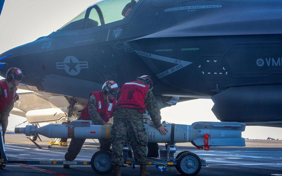 Cpl. Charlton Hale, Sgt. Cody Jackson and Lance Cpl. Hunter Soileau transport Guided Bomb Unit 12 Paveway II's to an F-35B Joint Strike Fighter on the flight deck of the British aircraft carrier HMS Queen Elizabeth while at sea, Sept.29, 2020.
