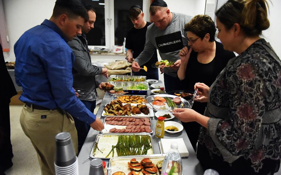 Soldiers and families fill their plates with traditional foods during a Passover celebration at Grafenwoehr, Germany, Friday, April 19, 2017.