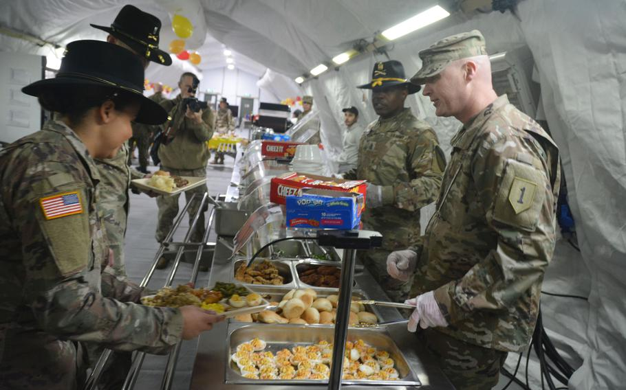 Command Sgt. Maj. Joshua C. Holthus, 1st Infantry Division Forward command sergeant major, serves Thanksgiving dinner to soldiers during a visit to Torun, Poland, on Nov. 27, 2019. Holthus and Col. Phil Brooks, 1st Infantry Division forward commander, were at Torun to visit the 3rd Battalion, 16th Field Artillery Regiment of the 2nd Armored Brigade Combat Team and bring a little holiday cheer to the deployed soldiers.