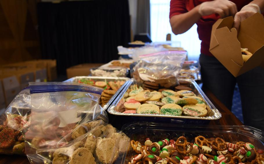 Volunteers choose from a variety of cookies to box up for single and unaccompanied service members during the annual holiday cookie drive at Ramstein Air Base, Germany, Dec. 12, 2019.