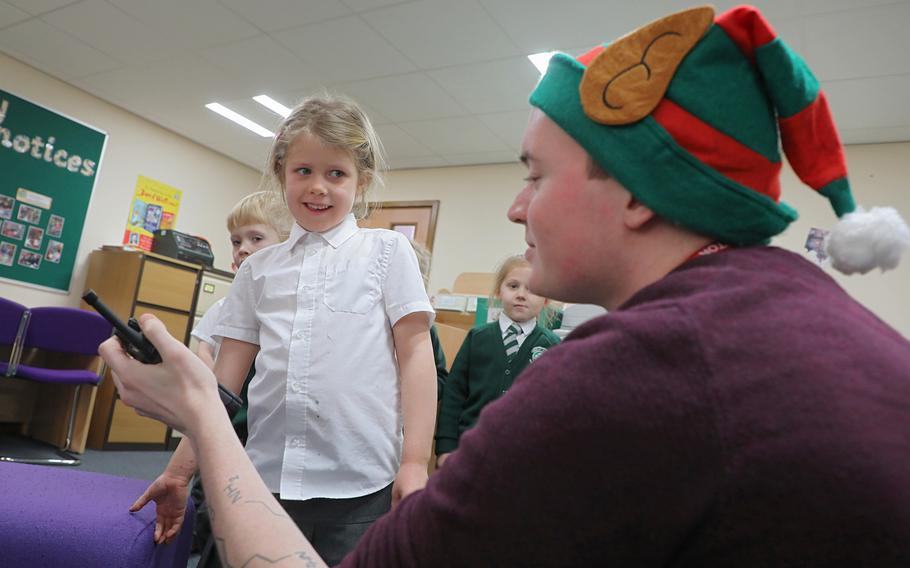 Amber Ramsey, 5, talks to Santa over a handheld radio held by Troy Knoke, a volunteer from the 48th Communications Squadron, Dec. 13, 2019, at Great Heath Academy in Mildenhall, England.