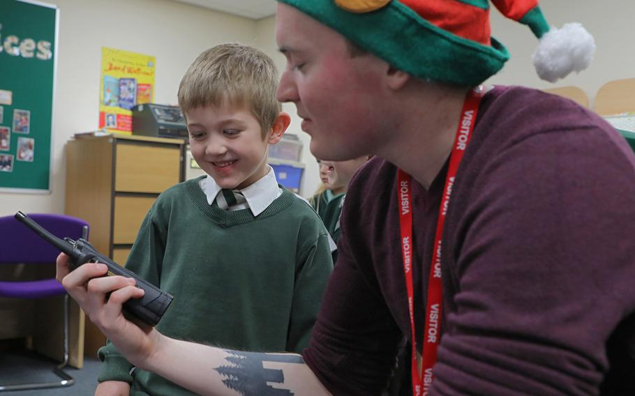 Jamie Liles, 5, talks to Santa over a handheld radio held by Troy Knoke, a volunteer from the 48th Communications Squadron on Dec. 13, 2019, at Great Heath Academy in Mildenhall, England.