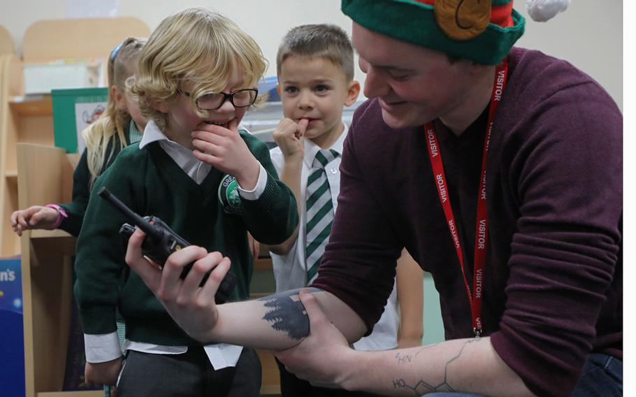 Jude Redman, 5, talks to Santa over a handheld radio held by Troy Knoke, a volunteer from the 48th Communications Squadron Dec. 13, 2019, at Great Heath Academy in Mildenhall, England.