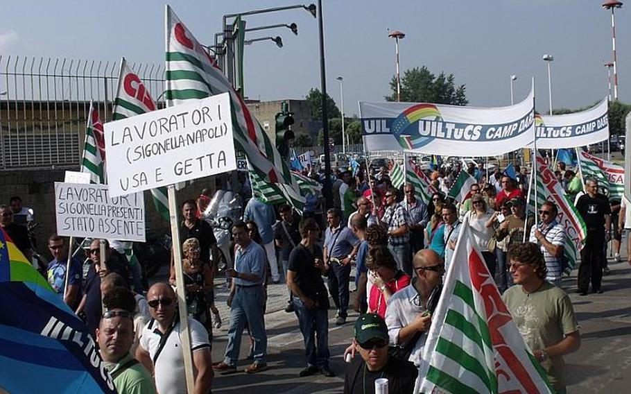 Hundreds of protesters from U.S. military installations around Italy gathered early Wednesday morning and marched to the front gate of the Capodichino base in Naples, Italy, to protest the February announcement of more than 90 job cuts affecting Italian employees in Naples and Sigonella.