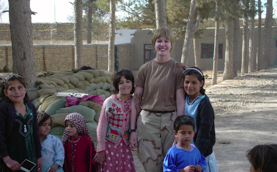 Jennifer Hunt, posing for a photograph with Afghan girls in 2005, was injured in a roadside bomb explosion in 2007 in Iraq. When she visited her local Department of Veterans Affairs hospital to seek treatment for pain, her young female doctor was surprised to learn that Hunt had been injured in combat.