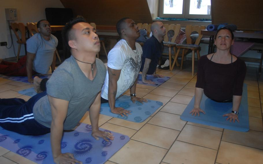 From left: Staff Sgt. Lincoln Manning, in background, 30, of New York; Sgt. Mark Coloma, 28, of Honolulu; Sgt. 1st Class Milton Johnson, 36, of Chicago and Staff Sgt. Neil Kessler, 32, of Albany, N.Y., learn yoga with the help of instructor Sarah Brown near Grafenwoehr, Germany on Wednesday.