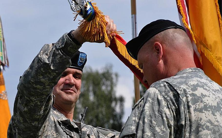 Col. Edward T. Bohnemann, commander of the 172nd Infantry Brigade, rolls up the unit's flag during a pre-deployment ceremony at the Army garrison in Grafenwoehr, Germany, on Saturday. The 172nd is heading to Afghanistan in the next few weeks.