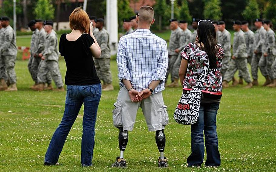 Brian Schar, a retired Army staff sergeant; his wife, Michelle; and a friend watch the 172nd Infantry Brigade march off the parade field at the Army garrison in Grafenwoehr, Germany, after a redeployment ceremony Saturday.