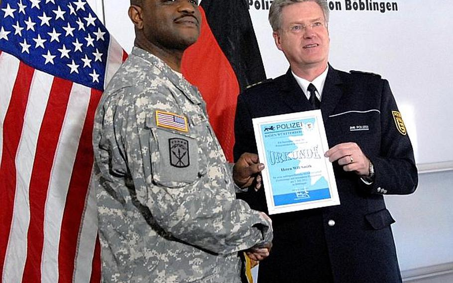 Spc. Willie Smith receives a certificate of appreciation from Rudi Denzer, chief of the Böblingen police department. Smith was credited with helping to save the lives of an elderly couple trapped in an apartment fire.