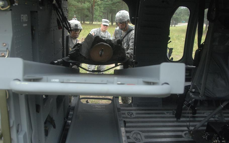 Sgt. John Rudegeair, Landstuhl Regional Medical Center, in patrol cap, watches as candidates for the Expert Field Medical Badge load a litter with a dummy into a helicopter at the Grafenwöhr Training Area. More than 300 candidates from a spectrum of medical occupations are training this week for the badge; testing begins Aug. 8.