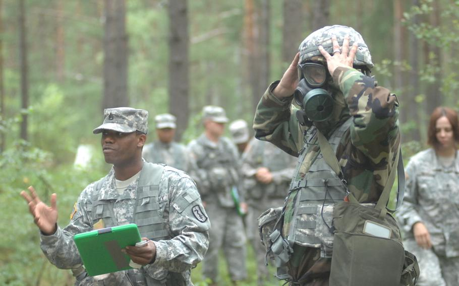 Sgt. Michael Tonjes, right, 8th Medical Logistics Company, demonstrates use of a gas mask and CBRN suit (Chemical-Biological-Radiological-Nuclear) as Staff Sgt. Timothy Miller of the 212th Combat Support Hospital describes each step to candidates for the Expert Field Medical Badge. More than 300 candidates from a spectrum of medical professions will test for the coveted badge at Grafenwöhr Training Area beginning Aug. 8.