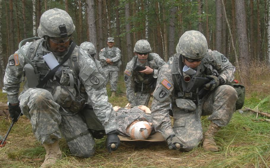 Cpl. Grady Clark, left, a medical supply specialist with the U.S. Army Medical Materiel Center in Pirmasens, Germany, prepares to lead soldiers along an obstacle course as part of training for the Expert Field Medical Badge at the Grafenwöhr Training Area. More than 300 candidates from a spectrum of medical occupations are training this week for the coveted badge; testing begins Aug. 8.
