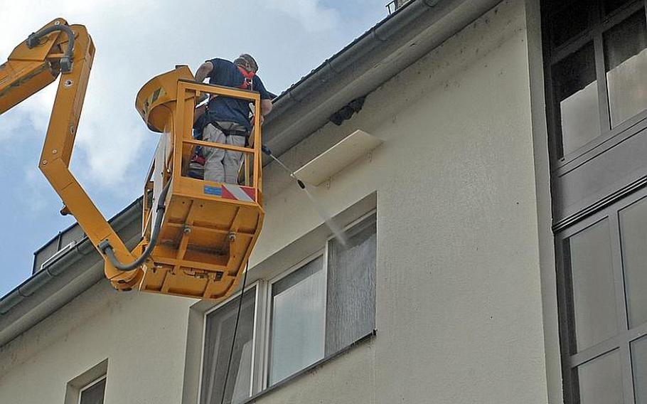 Workers for U.S. Army Garrison Baden Weurttemberg wash windows of a building on Patrick Henry Village last week after installing a board to catch droppings from nesting house martins. The birds' numbers have declined throughout Europe, and they and their nests, which they return to year after year, are protected in Germany and may not be removed. Six nests on the building were the first evidence of the birds' return to the area.