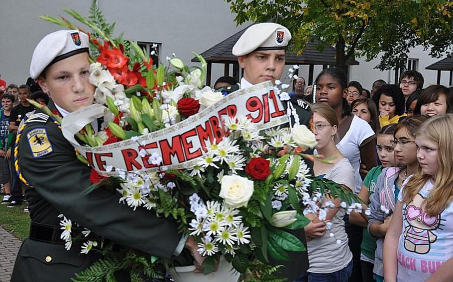 Cadets Nicholas Zurcher, a junior, and Daniel Riojas, a senior, carry a bouquet of flowers at the Bamberg Middle/High School Friday during a 9-11 remembrance ceremony.