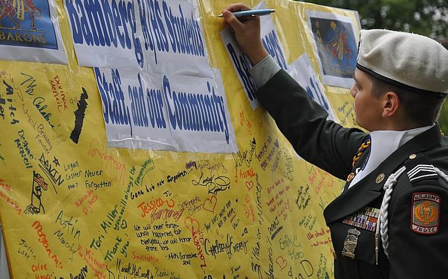 Cadet Staff Sgt. Daniel Riojas, a senior at Bamberg Middle/High Schoo, leaves a remembrance message prior to a 9-11 ceremony Friday at the school.