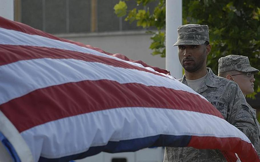 Senior Airman Bryant Lanier, from Springfield, Mass., folds the American Flag during a retreat ceremony to honor first responders on the 10th anniversary of Sept. 11, 2001. Lanier is assigned to the 48th Airspace Medicine Squadron at RAF Lakenheath, England.