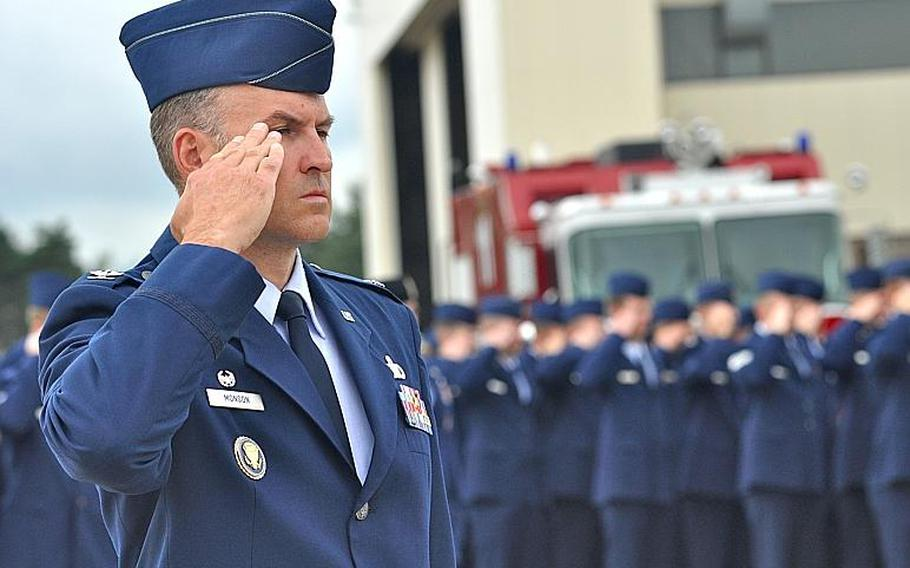 """Col. Michael Monson, commander of the 86th Mission Support Squadron, salutes during the playing of the """"Star-Spangled Banner"""" at a ceremony Friday at Ramstein Air Base commemorating the 10th anniversary of the attacks on Sept. 11."""