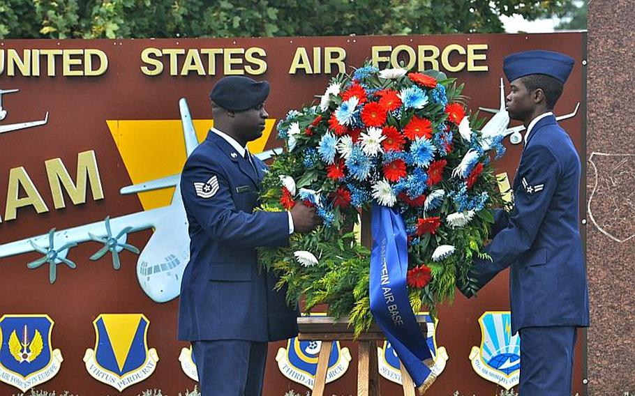 Two airmen remove a wreath from its pedestal during a ceremony Friday at Ramstein Air Base. The wreath, part of a ceremony commemorating 9/11, was placed at the foot of the flagpole, alongside another wreath that was brought by German officials.