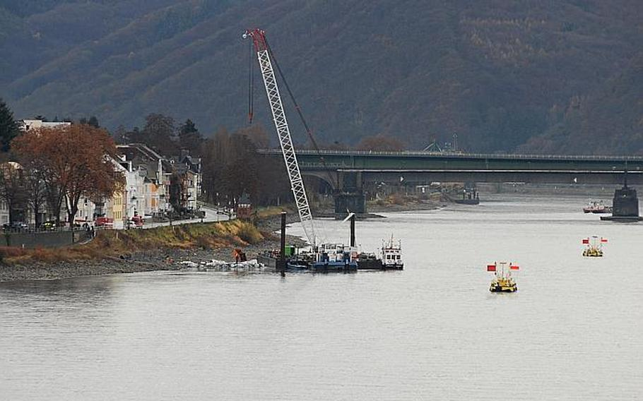 Workers began the task Dec. 4, 2011, of defusing a 4,000 pound bomb, dropped during World War II,  in Koblenz, Germany. Workers built sandbags around the bomb (pictured with the crane) to drain the water surrounding it. The flags mark an area where an American bomb and a grenade also were found recently in the Rhine River.