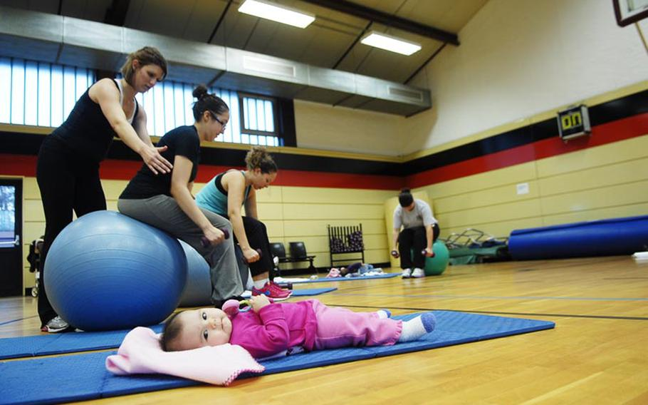 Amy Robitschek instructs Melissa Van Hausen how to properly sit on an exercise ball during a recent Binkies and Babes class at the Landstuhl Regional Medical Center fitness center in Germany. Van Hausen's 6-month-old baby was content to recline on a gym mat during the class. Binkies and Babes is one of several new classes the Army is offering in the Kaiserslautern area for parents and children.