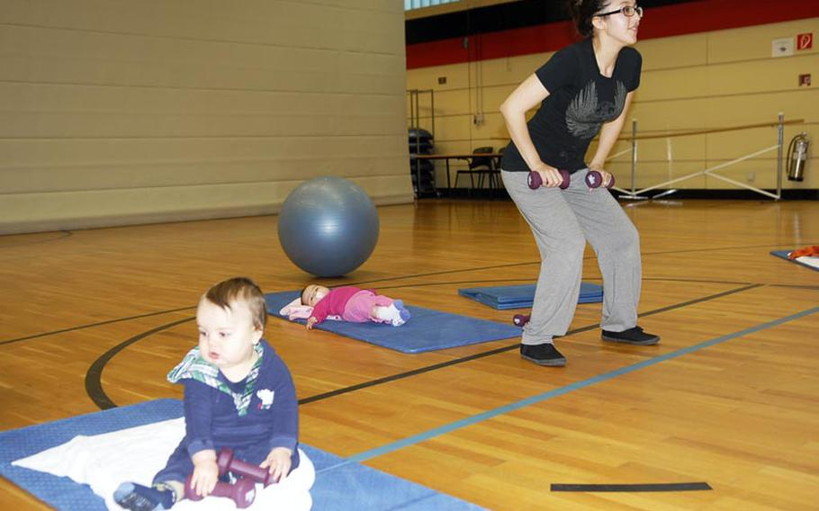 Melissa Van Hausen lifts weights while her baby daughter lies on a mat behind her and another baby plays with some weights during a recent Binkies and Babes class at the Landstuhl Regional Medical Center fitness center.