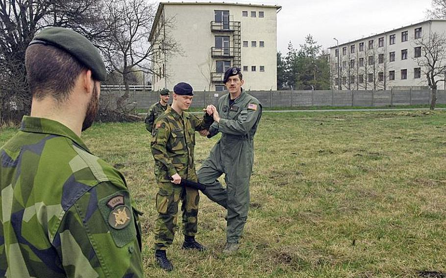 """Master Sgt. Frank Prebble gives instruction to Swedish and Norwegian members of the Heavy Airlift Wing's Raven Team. The Ravens are the security element for the C-17 crew, securing the areas around the plane upon landing. Most of the training, however, focuses on communication skills and using """"verbal judo"""" to resolve disputes that may occur in potentially hostile places."""