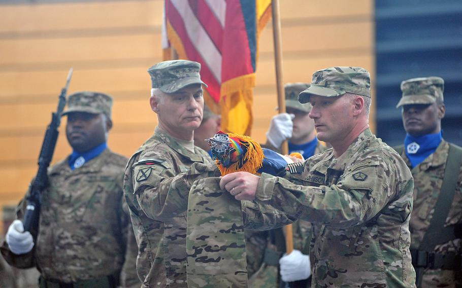Lt. Gen. James L. Terry, V Corps commander, left, and Command Sgt. Maj. William M. Johnson case the V Corps colors at a ceremony at Wiesbaden Army Airfield, Germany, on Thursday. The corps is headed for an Afghanistan deployment and is leaving Germany for good after more than 60 years.