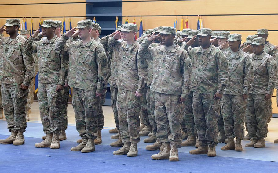 Soldiers of V Corps salute during the playing of the German and American national anthems at the V Corps casing of the colors ceremony at Wiesbaden Army Airfield, Germany, on Thursday. The corps is headed for an Afghanistan deployment, and is leaving Germany for good after more than 60 years.