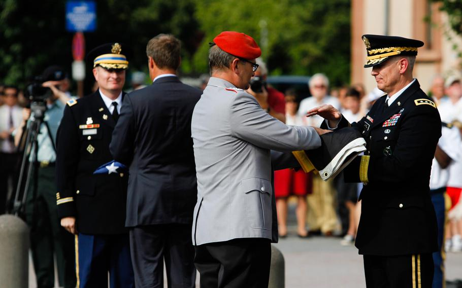 German Col. Wolfgang Mika hands the last German flag flown at the Army's Campbell Barracks in Heidelberg to Lt. Gen. Donald M. Campbell Jr., the commander of U.S. Army Europe. Behind then, garrison commander Col. Brian DeCoster hands the last American flag flown here to Heidelberg Mayor Eckart Wuerzner. Until earlier this year, the base was USAREUR's headquarters. A number of bases in the city will soon be handed over to German authorities, ending the American presence here after almost seven decades.