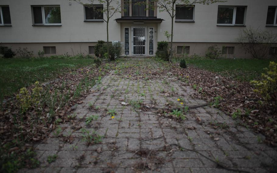 After sitting unoccupied for months, a sidewalk to a housing unit at the U.S. Army's Mark Twain Village in Heidelberg, Germany, is choked with weeds, leaves and twigs.