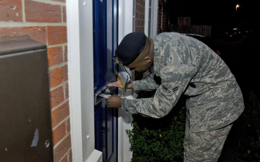 Airman 1st Class Terence Sanford, with the 100th Air Refueling Wing, stuffs leaflets through a mail slot in a home in Suffolk, Wednesday, Sept. 18, 2013. Members of the patrol provided leaflets to homes in an effort to educate people about crime prevention.