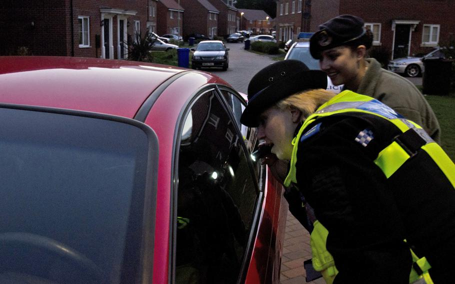 Anne-Marie Powell, Suffolk police community support officer, and Senior Airman Kiirstyn Williams, with the 48th Fighter Wing, inspect a car in Suffolk, England, Wednesday, Sept. 18, 2013. Their inspection was part of a safety patrol to warn people about the dangers of leaving their vehicles unlocked and leaving valuables on display.