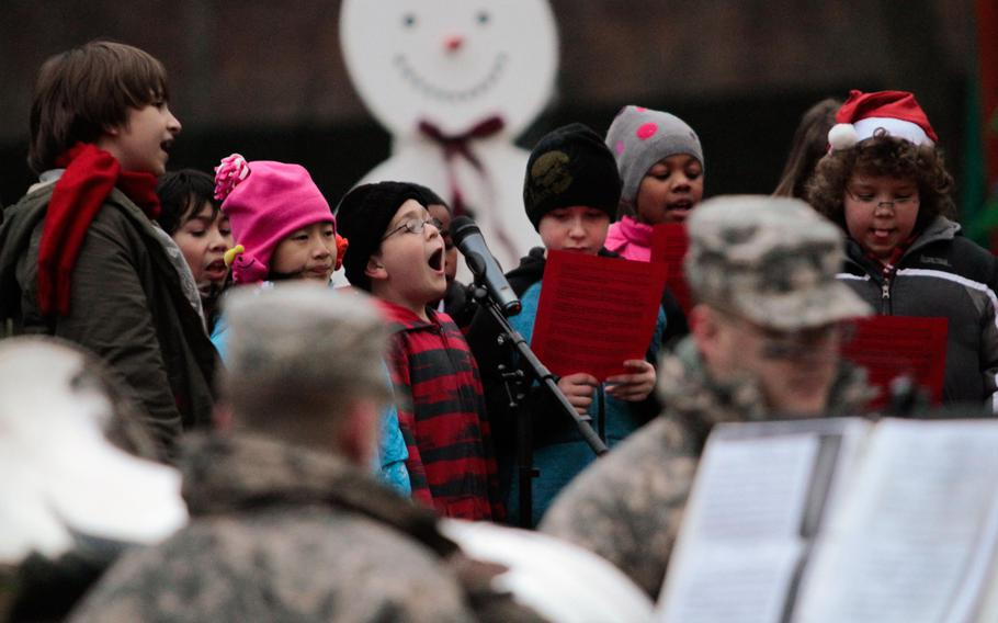 Students from Kaiserslautern Elementary School sing holiday carols at the 21st Theater Sustainment Command's tree lighting ceremony Wednesday, Dec. 4, 2013, at Panzer Kaserne in Kaiserslautern, Germany.
