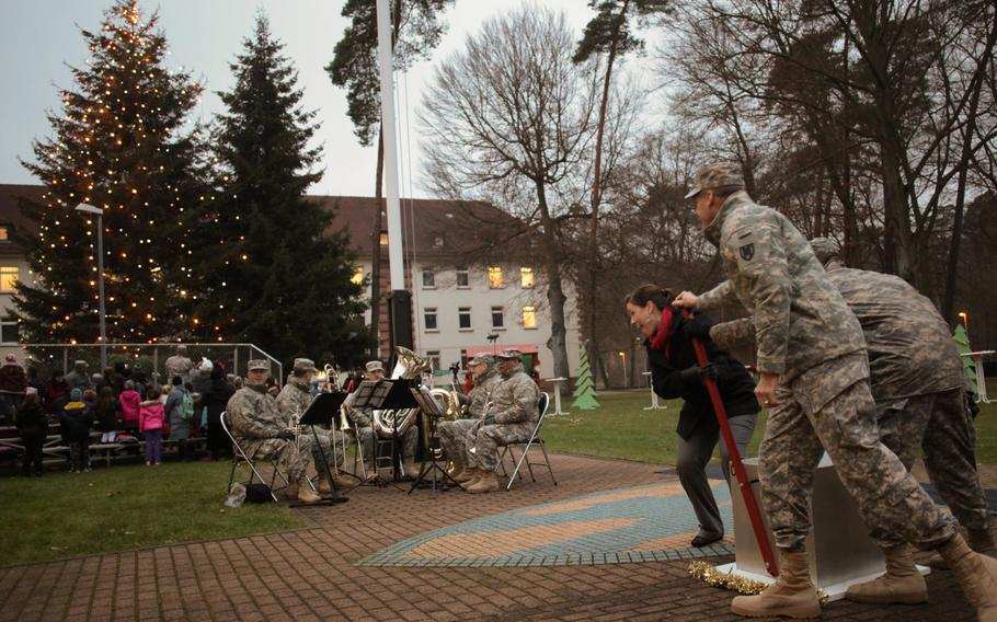 Maj. Gen. John O'Connor, commander of the 21st Theater Sustainment Command, along with Amy Rodick and Sgt. Baran Pourtahmaseb-Sasi flip a giant switch at a holiday tree lighting ceremony Wednesday, Dec. 4, 2013, at Panzer Kaserne in Kaiserslautern, Germany.
