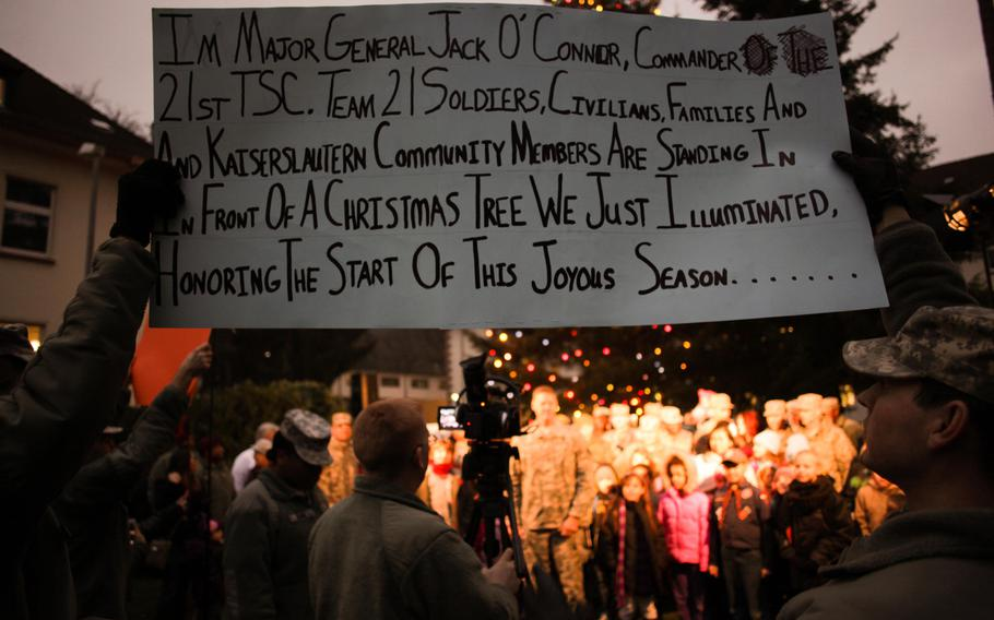 Soldiers hold up cue cards for the commander, soldiers and families of the 21st Theater Sustainment Command to read from as they record a commercial that will be broadcast to U.S. forces overseas during a tree lighting ceremony Wednesday, Dec. 4, 2013.