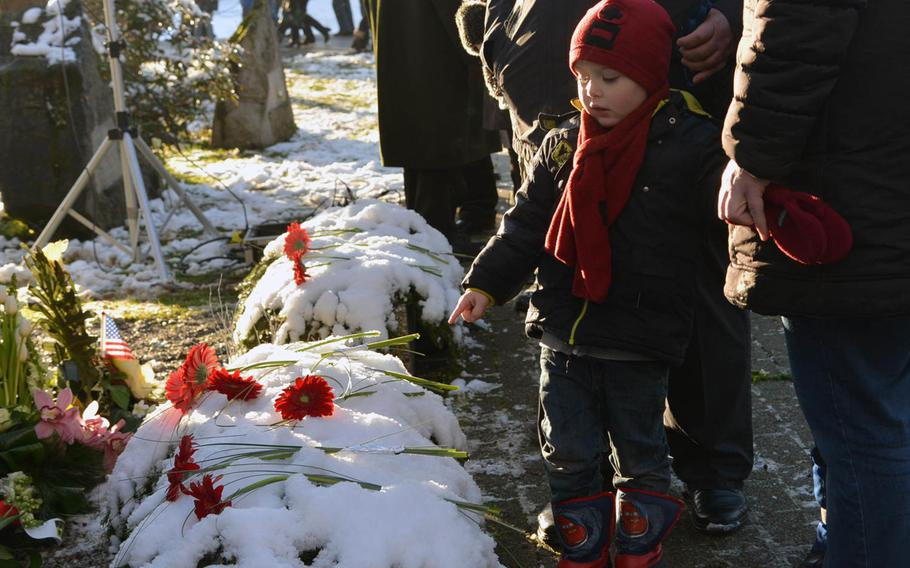 A Belgian boy points to flowers left by school children during a ceremony marking the 70th anniversary of the Malady massacre Sunday, Dec. 14, 2014. On Dec.17, 1944, in Baugnez, Belgium, Nazi SS troops killed 84 American prisoners of war during the Battle of the Bulge. Baugnez is a suburb of Malmedy.
