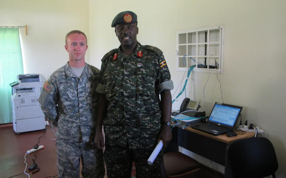 Pvt. Cody Mitchell poses for a photograph with Ugandan Brig. Gen. Matthew Gureme during the military exercise Eastern Accord in Jinja, Uganda.Gureme was exercise director.