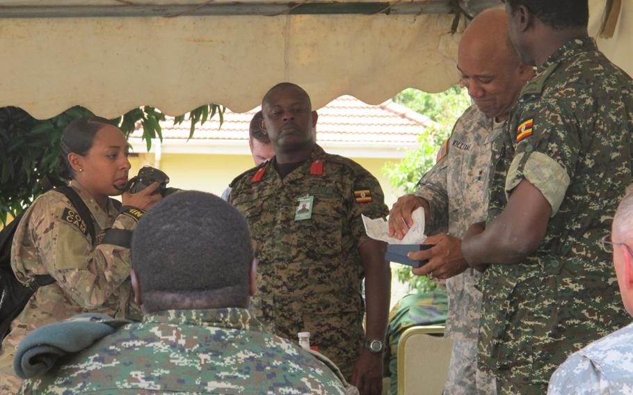 U.S. Army Africa commander Maj. Gen. Darryl Williams exchanges gifts with a Ugandan general during the annual Eastern Accord exercise in Jinja, Uganda. Ugandan Brig. Gen. Matthew Gureme, center, is the exercise's director.