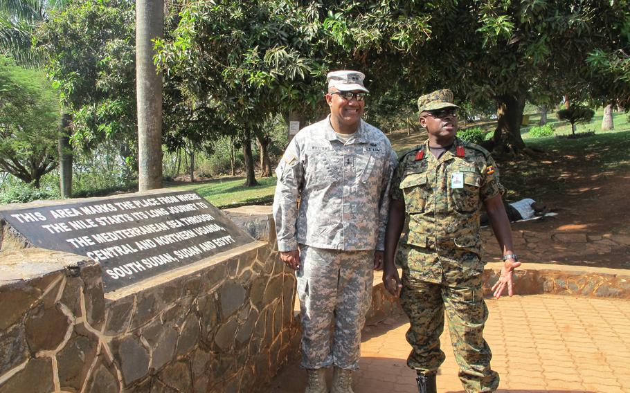 U.S. Army Africa commander Maj. Gen. Darryl Williams and  Ugandan Brig. Gen. Matthew Gureme pose at a plaque at a local tourist attraction: the source of the Nile River.